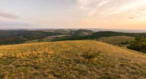 Zmierzch krajobrazowa panorama, wzgórza w złotej godzinie, mała wioska w dolinie, piękni kolory i chmury, Zdjęcia Stock