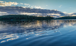 Zmierzch na Jeziornym Ladoga słońcu za chmurami Odbicie Zdjęcia Stock