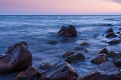 Zmierzch na morzu. W pierwszoplanowych wielkich głazach. Zdjęcia Stock