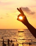 Zmierzch na plaży i palca zając z słońcem ono przygląda się Zdjęcie Royalty Free