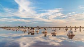 Zmierzch na różowym słonym jeziorze, poprzednia kopalnia dla ekstrakci menchii sól rząd drewniani czopy przerastający z solą fotografia royalty free