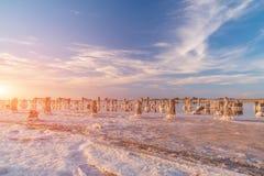 Zmierzch na różowym słonym jeziorze, poprzednia kopalnia dla ekstrakci menchii sól rząd drewniani czopy przerastający z solą zdjęcie royalty free