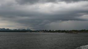 Zmierzch nad burzowymi chmurami przez wodę zdjęcia stock