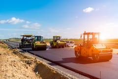 Zmierzch nad drogowy rolownik pracuje na budowie Zdjęcie Royalty Free