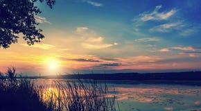 Zmierzch nad jeziorem kolorowe chmury w niebie, odbijającym w wodzie malownicza, dramatyczna scena, zdjęcie royalty free