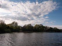 Zmierzch nad jeziorem w wiośnie z chodzenie fala chmurą i czochrami Obrazy Stock