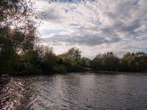 Zmierzch nad jeziorem w wiośnie z chodzenie fala chmurą i czochrami Zdjęcie Stock