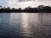 Zmierzch nad jeziorem w wiośnie z chodzenie fala chmurą i czochrami Obraz Stock