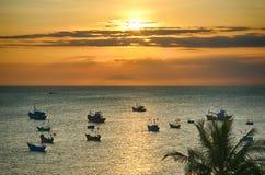 Zmierzch nad morzem słońce błyszczy między chmurami, łodzie rybackie jest widoczny morze obrazy stock