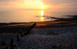 Zmierzch nad oceanem. drewniani falowi łamacze prowadzi słońce Zdjęcia Stock