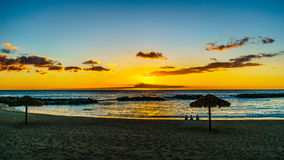 Zmierzch nad plażą z pokrywającymi strzechą parasolami pod niebieskim niebem na zachodnim wybrzeżu Oahu i laguną zdjęcie royalty free