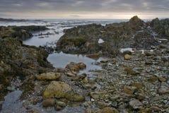 Zmierzch nad skalistej plaży wodą fotografia stock