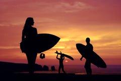 Zmierzch przy linią brzegową, rodzina z ich surfboards zdjęcie royalty free