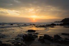 Zmierzch przy skalistą plażą Zdjęcie Stock