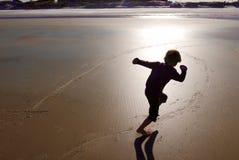 Zmierzch sylwetka młody chłopiec bieg na plażowym piasku fotografia stock
