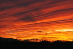 Zmierzch w blask pomarańcze i jaskrawy żółty zamiatać przez niebo w smugach Zdjęcie Royalty Free
