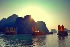 Zmierzch w Halong zatoce z żeglowanie dżonkami Fotografia Royalty Free