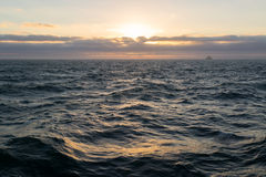 Zmierzch w morzu z ładunku statkiem na horyzoncie Zdjęcie Royalty Free