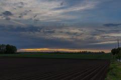 Zmierzch z dramatycznym niebem nad rolniczymi polami w Vroenhoven zdjęcie stock