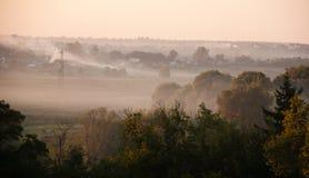 Zmierzch z mgłą, dym i słońce wzrasta nad wioską Zdjęcia Royalty Free