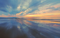 Zmierzch z odbiciem na piasku z drobnym zoomu blura Obrazy Royalty Free