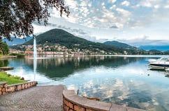 Zmierzchu krajobraz Lavena Ponte Tresa z fontanną i odbiciami w jeziorze Lugano Zdjęcie Stock