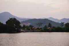Zmierzchu krajobraz z nieociosaną azjatykcią wioską Złoty godzina widok na kambodżańskich budach w górze Wciąż mglisty i rzeczny  zdjęcie royalty free