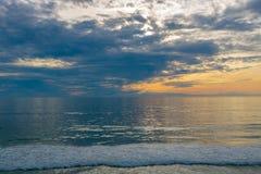 Zmierzchu seascape, pomarańcze, błękit, żółty niebo z aqua morskim zielonym morzem, biel macha kołysanie się wewnątrz, pokojowy o zdjęcie stock