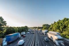 Zmierzchu widoku ciężkiego ruchu drogowego chodzenie przy prędkością na UK autostradzie w Anglia obrazy stock