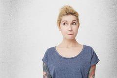 Zmieszana i oszołamiająca śliczna dziewczyna, jest ubranym błękitną przypadkową koszulkę, przebijającego nos i tatuaże, patrzeje  obrazy stock