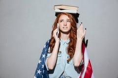 Zmieszana rudzielec młodej damy mienia książka na głowie Fotografia Stock