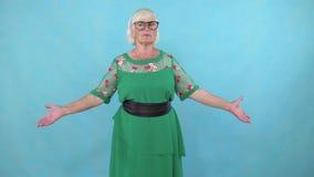 Zmieszana starsza kobieta z szkło stojakami na błękitnym tle zdjęcie wideo