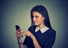Zmieszana wzburzona kobieta patrzeje jej telefon komórkowego Zdjęcia Royalty Free