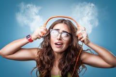 Zmieszana zdziwiona dziewczyna słucha muzyka w hełmofonach zdjęcia stock