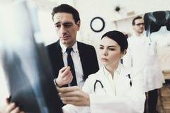 Zmieszani biznesmenów spojrzenia przy prześwietleniem kości Radiolog robi diagnozie zdjęcie stock