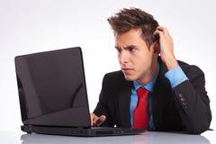 Zmieszani mężczyzna spojrzenia przy laptopem fotografia stock