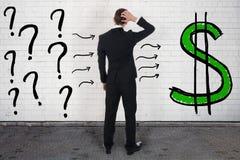 Zmieszany biznesmen Patrzeje znaki zapytania I Dolarowego znaka zdjęcia stock