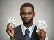 Zmieszany biznesmen trzyma dolara, euro rachunki zdjęcia stock