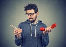 Zmieszany mężczyzna z starymi i nowymi telefonami zdjęcia stock