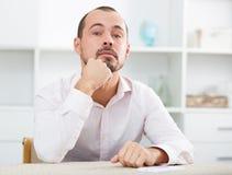 Zmieszany młody człowiek przy miejscem pracy Zdjęcia Stock