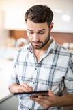 Zmieszany młody człowiek używa cyfrową pastylkę w kuchni Obraz Royalty Free