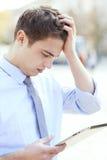 Zmieszany mężczyzna patrzeje cyfrową pastylkę Fotografia Royalty Free