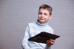 Zmieszany nastoletni chłopak z pastylka komputerem osobistym w jego rękach Technologia, w ten sposób fotografia royalty free