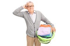 Zmieszany senior trzyma pralnianego kosz obraz royalty free