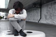 Zmieszany skołowany młody Azjatycki biznesowy mężczyzna siedzi jego kolana i ściska do klatki piersiowej fotografia royalty free