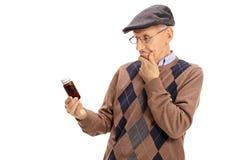 Zmieszany starszy patrzejący butelkę pigułki Obraz Stock