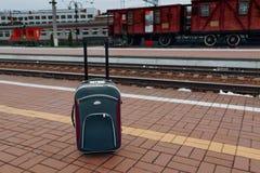 Zmrok - błękitna walizka na koło stojakach na taborowej wyjściowej platformie, tło odbicia, fotografia royalty free
