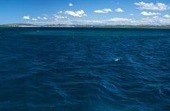 Zmrok - błękitnego seawater nawierzchniowa i odległa linia brzegowa Zdjęcie Stock