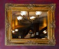 Zmrok - czerwony faux malujący marbilized ścianę z ozdobnym złotym lustrem odbija ciepłego nieociosanego pokój z oprawą oświetlen fotografia stock