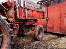 Zmrok - czerwony grunge tło z częścią stary zaniedbany ciągnik z gum brudnymi kołami zdjęcia stock